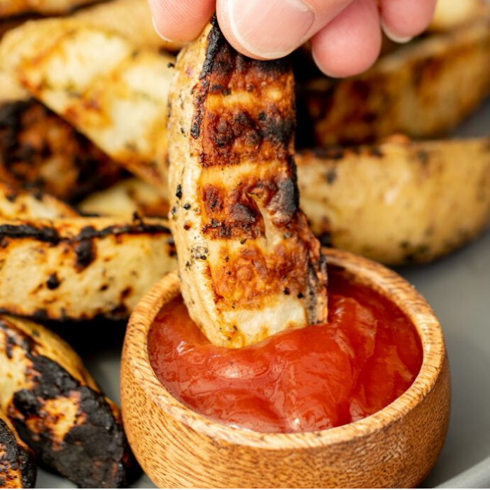 Single grilled potato wedge being dipped into ketchup with a pile of grilled potato wedges in the background.