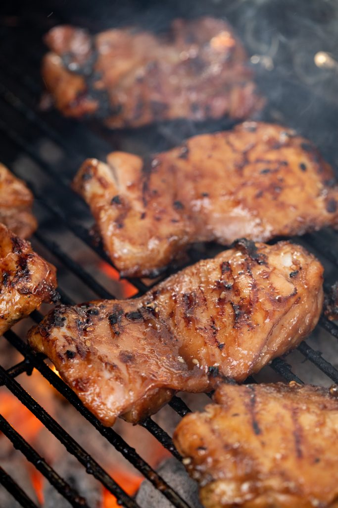 5 teriyaki chicken thighs on grill grates with hot charcoal directly underneath