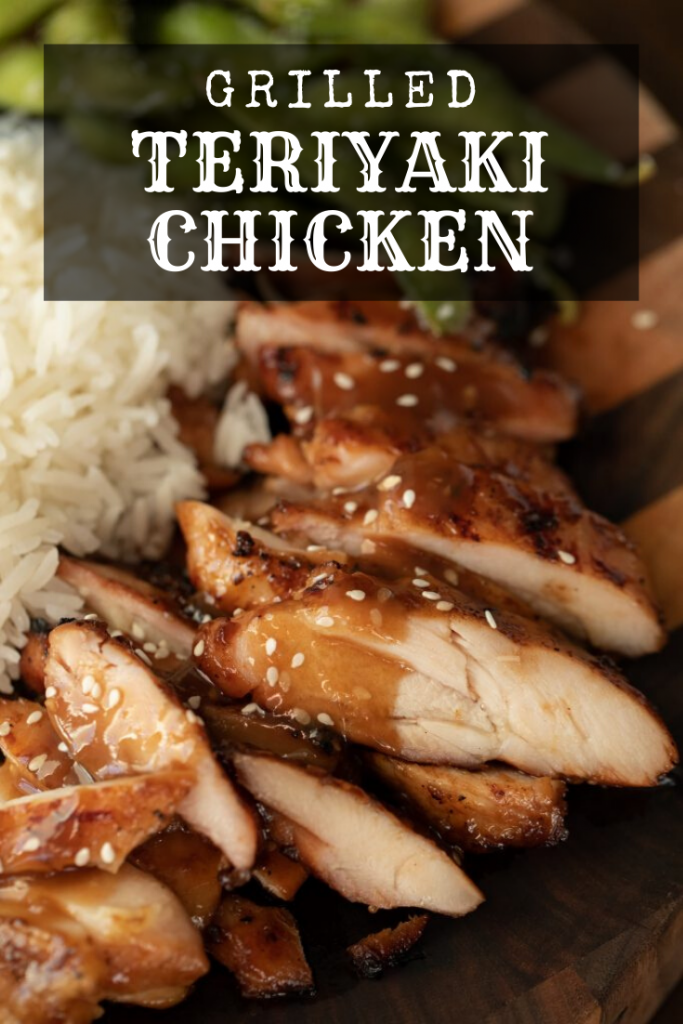 Sliced grilled teriyaki chicken thighs topped with teriyaki sauce and sesame seeds. Plated on a wood board alongside a pile of white rice.