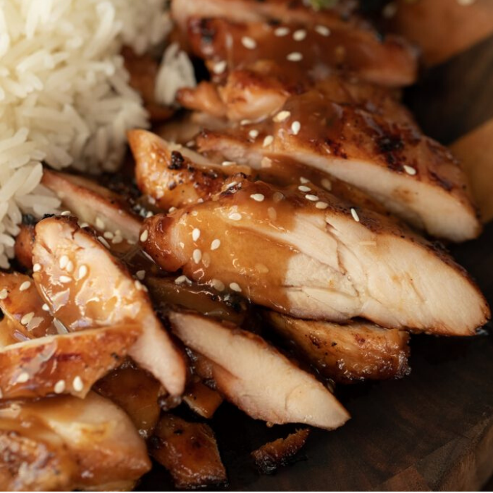 Sliced teriyaki chicken arranged on a wood cutting board and topped with teriyaki sauce.