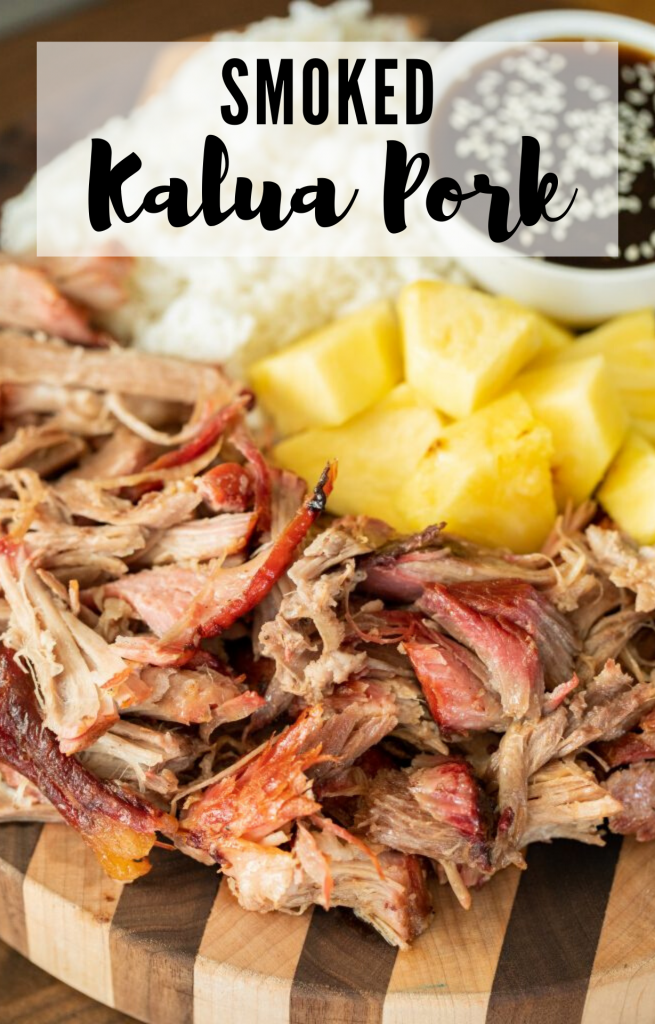 "Vertical image of shredded smoked kalua pork arranged on a wood cutting board with pineapple chunks, rice, and a bowl of teriyaki sauce in the background. Decorative text says ""smoked kalua pork"""