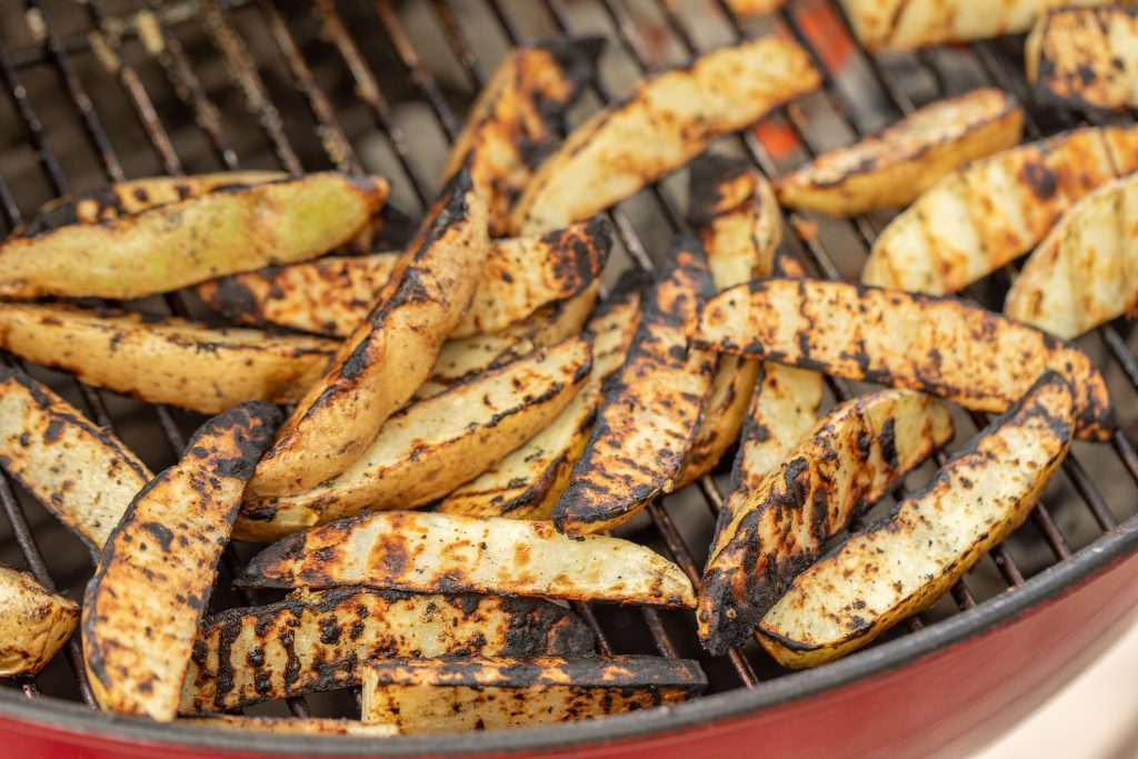 Grilled potato wedges on the grill grates of a charcoal grill.