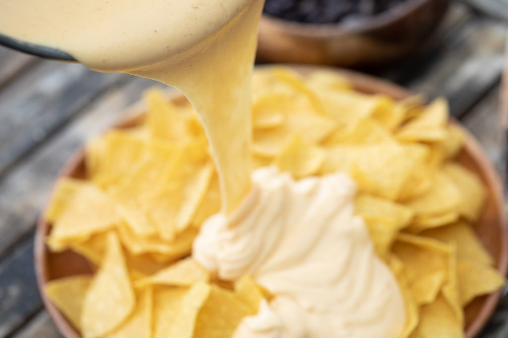 Nacho cheese sauce being poured from a pan onto a pile of tortilla chips