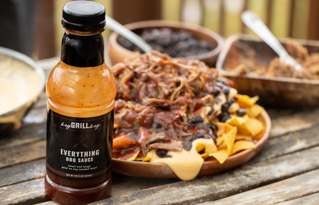 Bottle of Hey Grill Hey Everything sauce in the foreground of the photo. Plate of pulled pork nachos and bowls of pork, black beans, and cheese sauce in the background