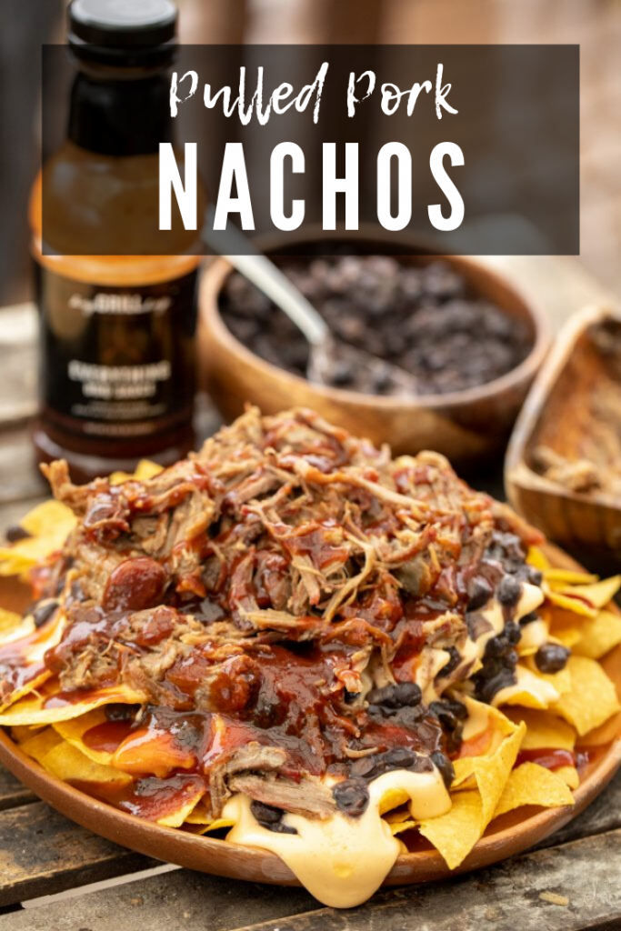Pulled pork, bbq sauce, black beans, and cheese sauce layered on top of tortilla chips on a wooden plate with bottle of BBQ sauce and bowl of extra black beans in the background with decorative text