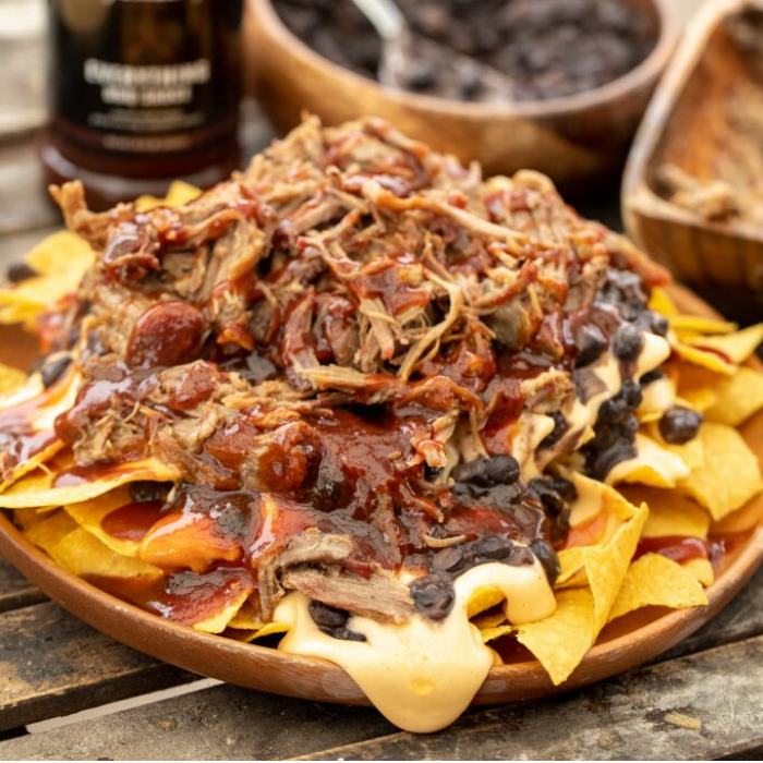 Pulled pork nachos on a wooden plate with a bottle of Everything Sauce and bowl of black beans in the background.