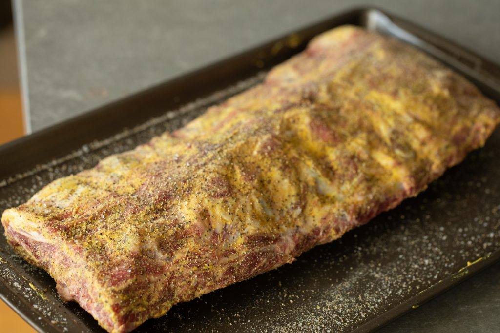 Rack of beef back ribs on a metal baking sheet, slathered in mustard and seasoned with Beef Seasoning