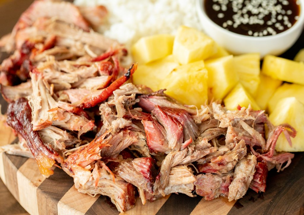 Shredded kalua pork on a wood cutting board in the foreground with pineapple chunks, rice, and a small bowl of teriyaki sauce in the background