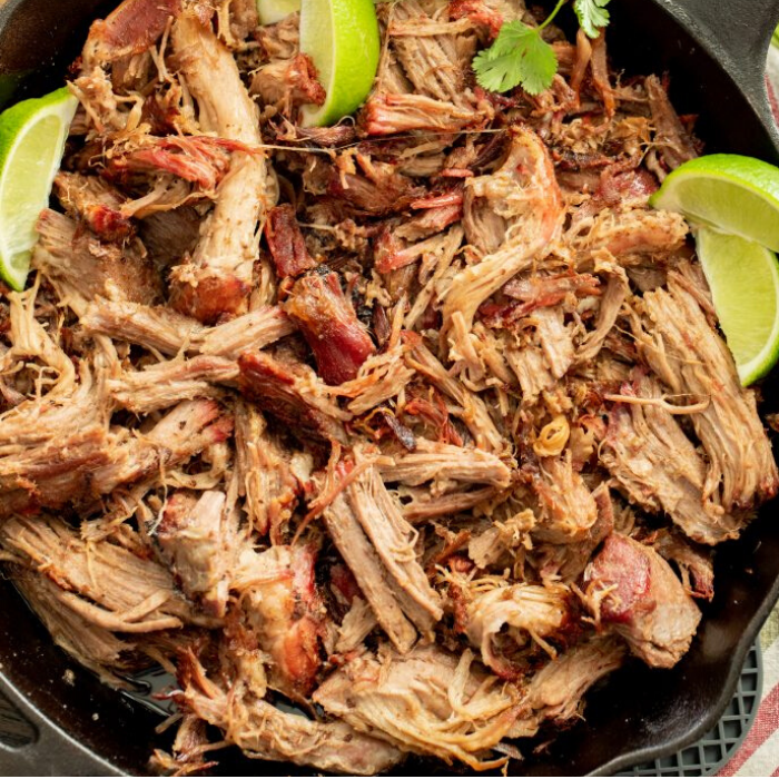 Shredded smoked pork carnitas in a cast iron skillet garnished with lime wedges.