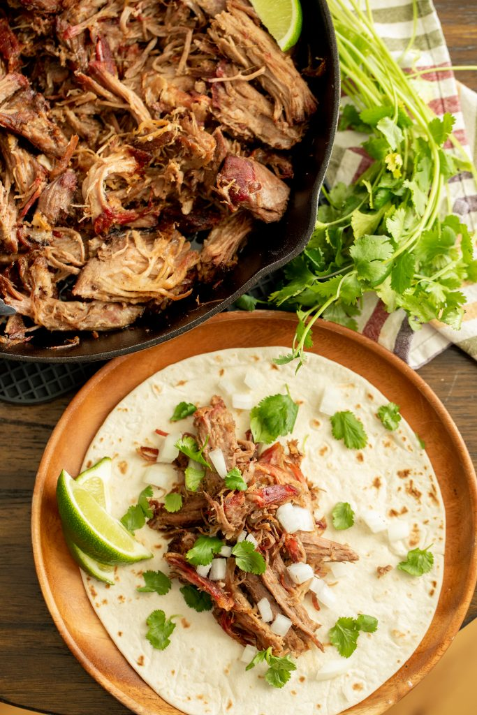 Shredded smoked pork carnitas on a flour tortilla in a wooden serving bowl next to a cast iron skillet full of shredded pork carnitas.