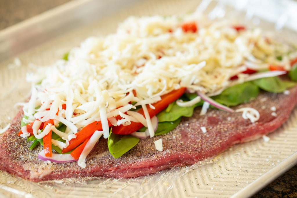 Flattened flank steak on a piece of plastic wrap sitting on a metal baking sheet. Flank steak is seasoned and topped with uncooked spinach, roasted bell pepper strips, red onions, and a pile of shredded mozzarella cheese.