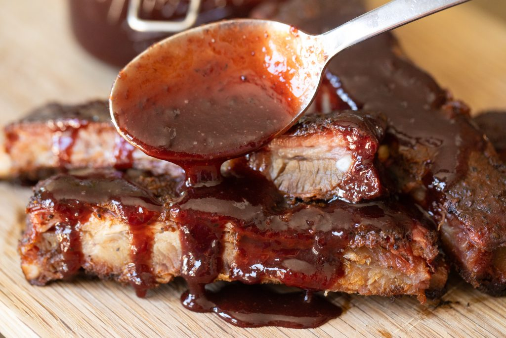 Spoonful of cherry cola BBQ sauce being drizzled over smoked ribs.