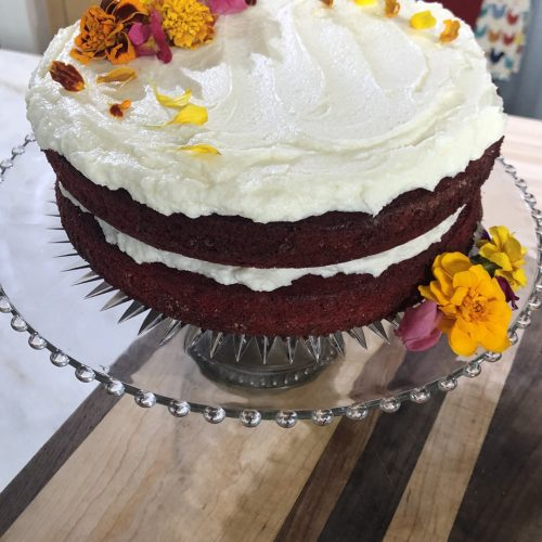 Red Velvet Cake with Ermine Frosting and Fresh Flowers. on a wooden table.