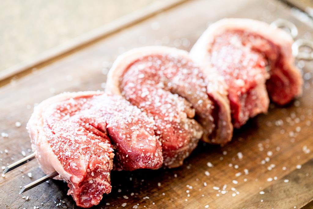 Raw, skewered picanha steaks seasoned with coarse salt on a wood cutting board.