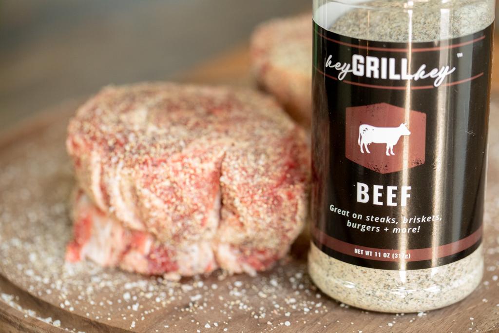Side shot of raw, tied ribeye cap steak that is seasoned with Hey Grill Hey Beef Rub. Bottle of Hey Grill Hey Beef Rub next to the steak. All on a wood cutting board.