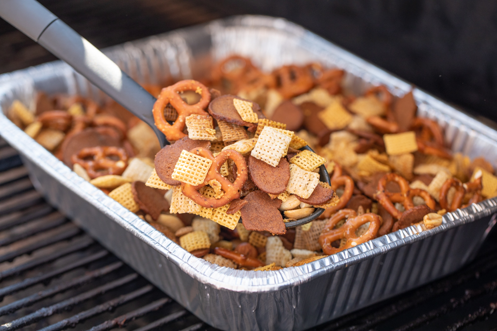 Spoonful of smoked chex mix over an aluminum pan of smoked chex mix on the grill grates of a smoker.