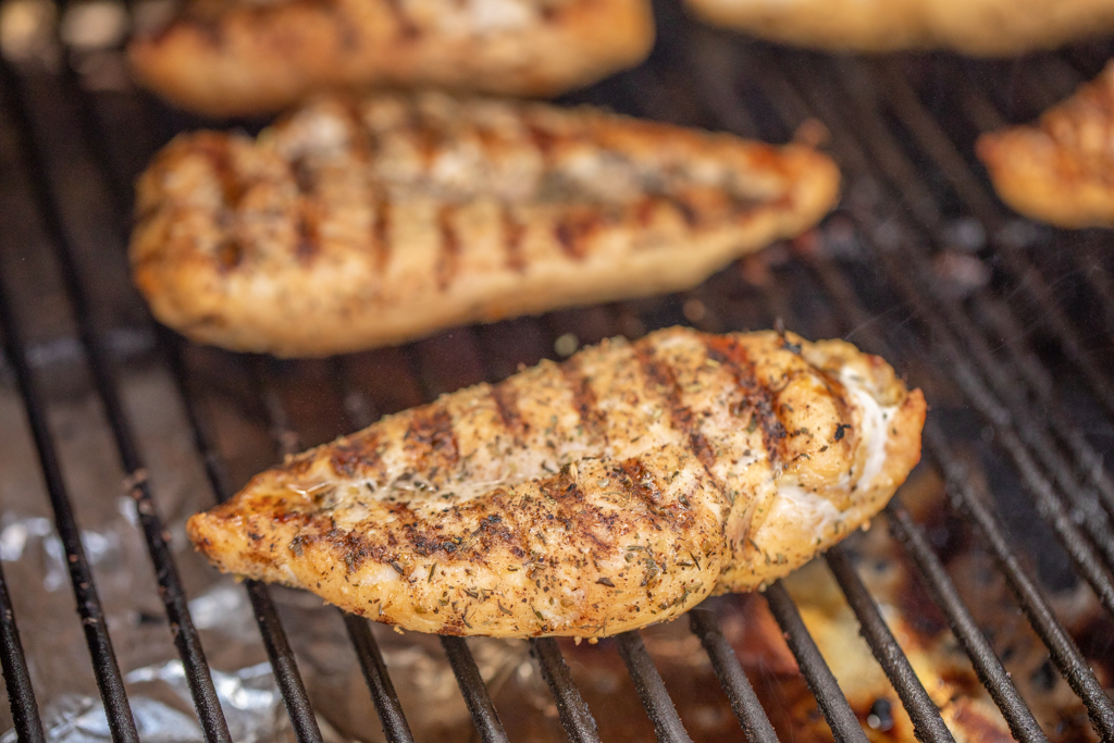 Seasoned chicken breast on grill grates with grill marks