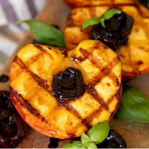 Two grilled peaches on a wooden cutting board garnished with fresh basil and dark cherries.
