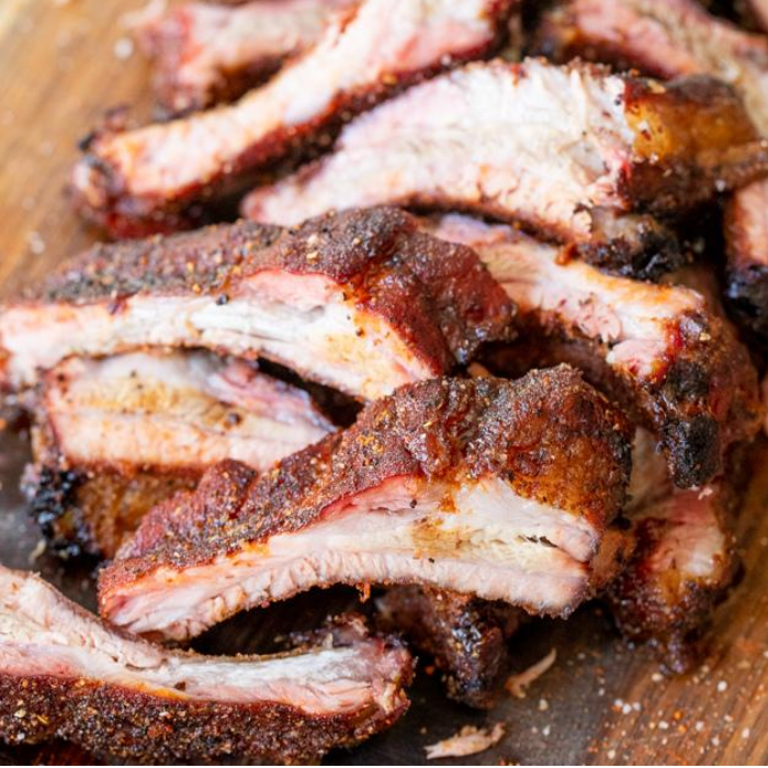 Sliced Memphis style dry rub ribs arranged in a pile on a wood cutting board.