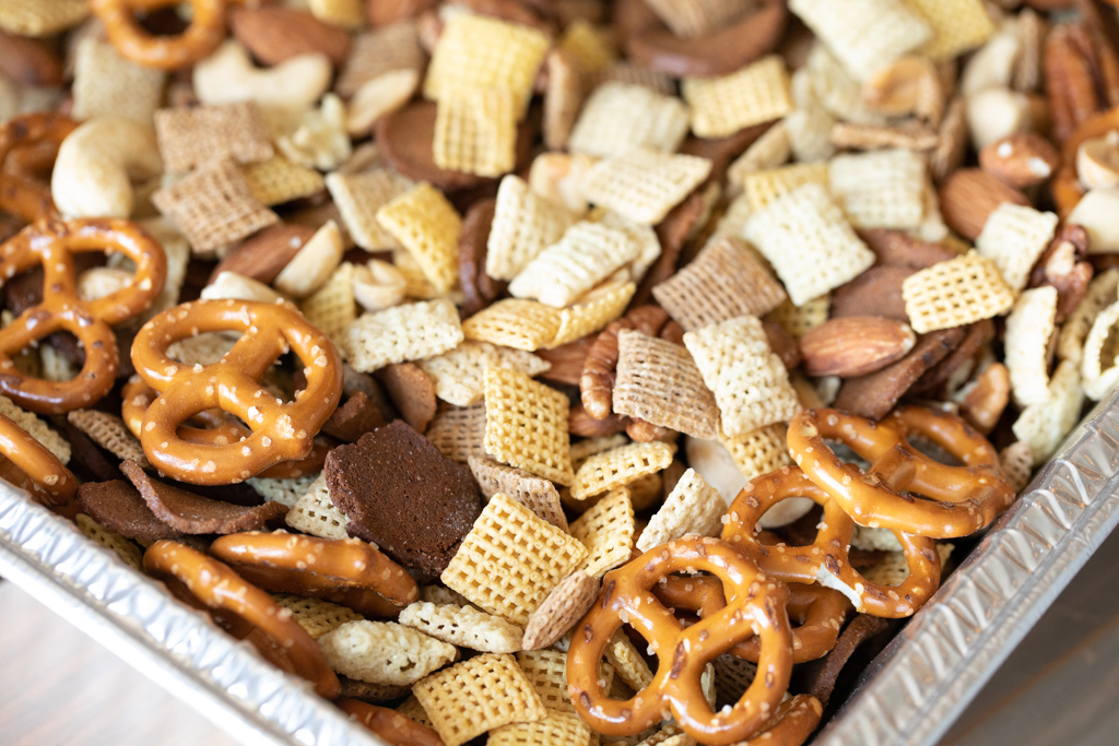 Chex cereal, mini pretzels, mixed nuts, and rye chips mixed in a disposable aluminum pan.