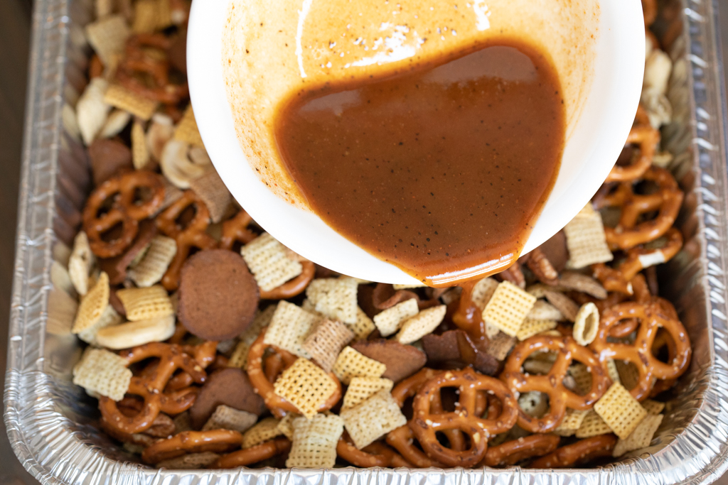 White bowl of melted butter, Worcestershire sauce, and Sweet Rub being poured over Chex snack mix.