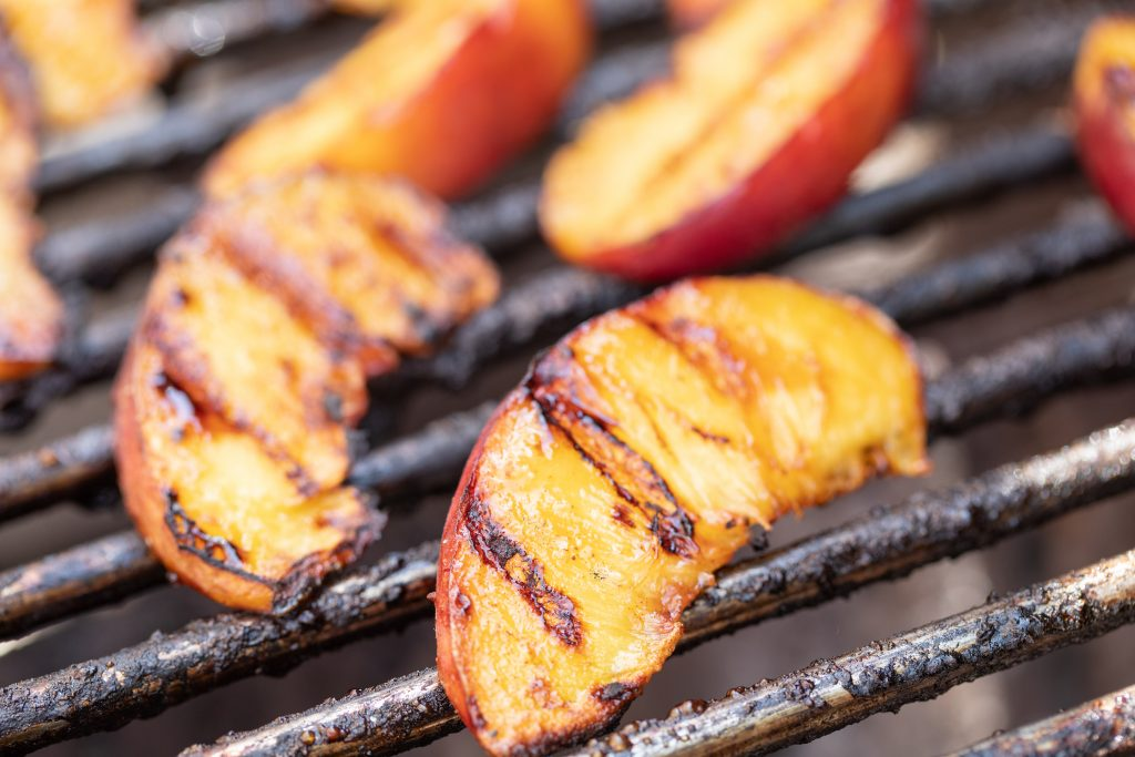 Sliced grilled peaches on the grill grates of a grill.