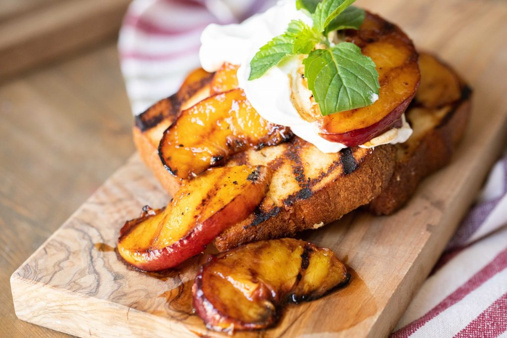 Grilled pound cake topped with grilled peaches, whipped cream, and mint leaves on a wooden cutting board.