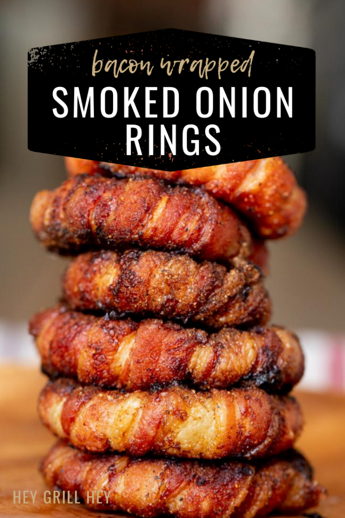 A stack of onion rings wrapped in bacon on a wooden cutting board