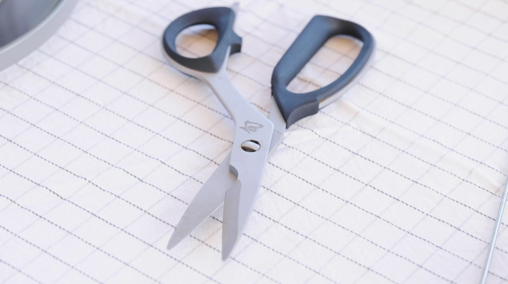 Kitchen shears on a white tablecloth.