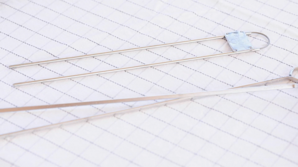 Metal skewers on a white tablecloth.