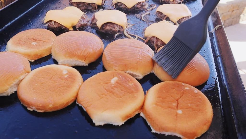 Burger buns and burger patties topped with American cheese on a flat top griddle.
