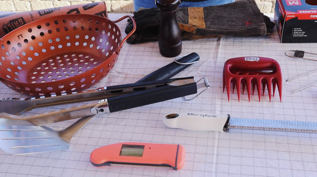 Butcher paper, grill basket, tongs, spatula, meat thermometer, grater, meat claws, and leather gloves on a table.