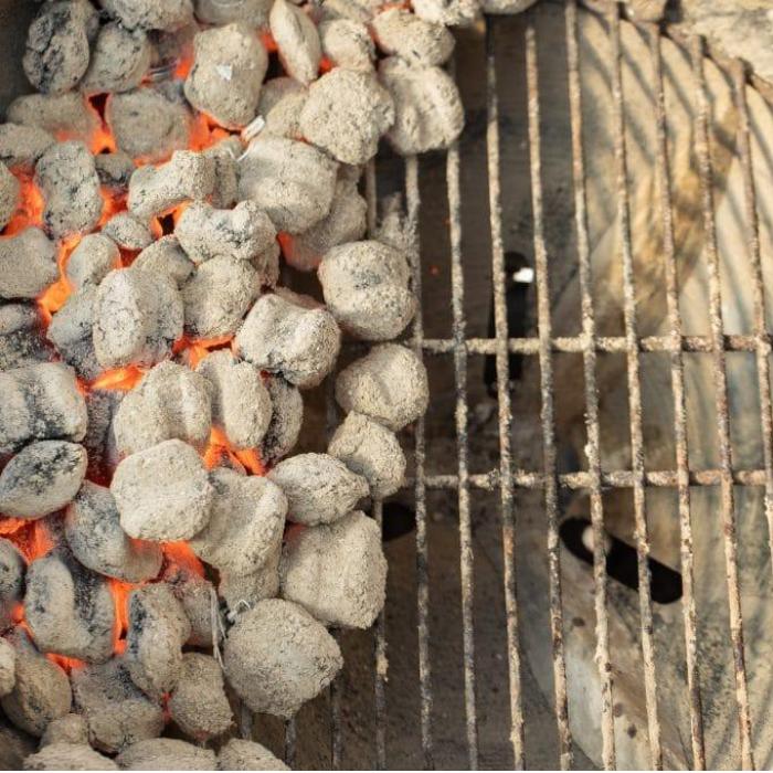 Hot coals on half of a charcoal grill.