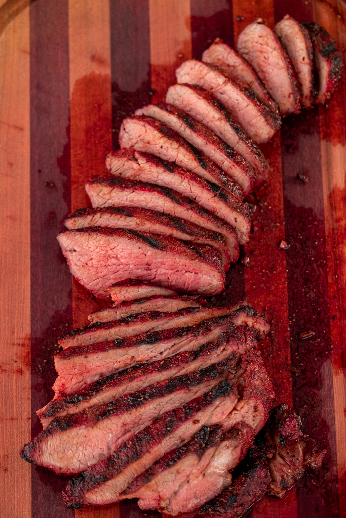 Sliced coffee rub tri tip on a wooden cutting board.