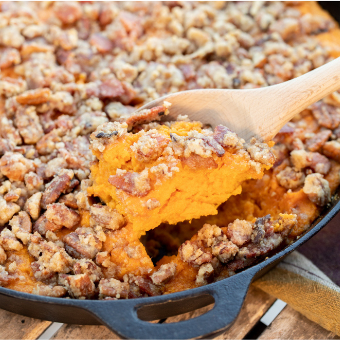 Wooden spoon taking a scoop out of a sweet potato casserole.