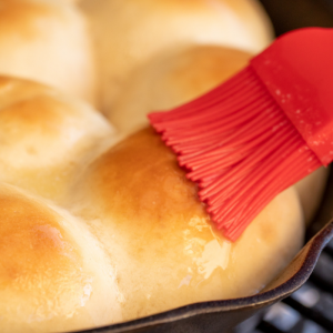 Red basting brush spreading melted butter on golden brown grilled rolls.