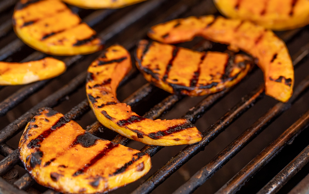 Sliced butternut squash on the grill grates of a grill.