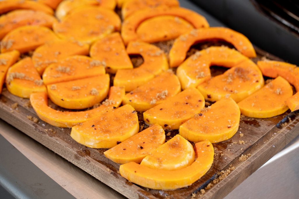 Sliced and seasoned butternut squash on a cutting board.