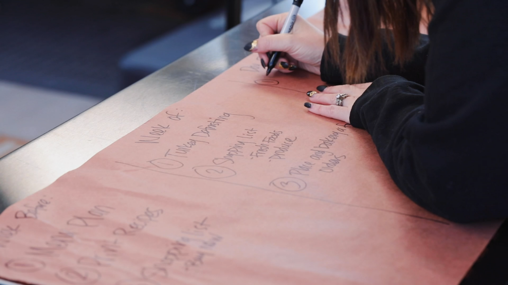 Susie writes a list of items to complete the week of Thanksgiving on peach butcher paper.