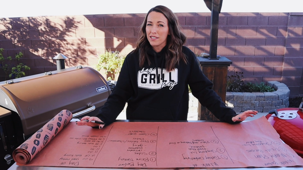 Susie stands in front of a large piece of butcher paper with a Thanksgiving meal plan written on it.