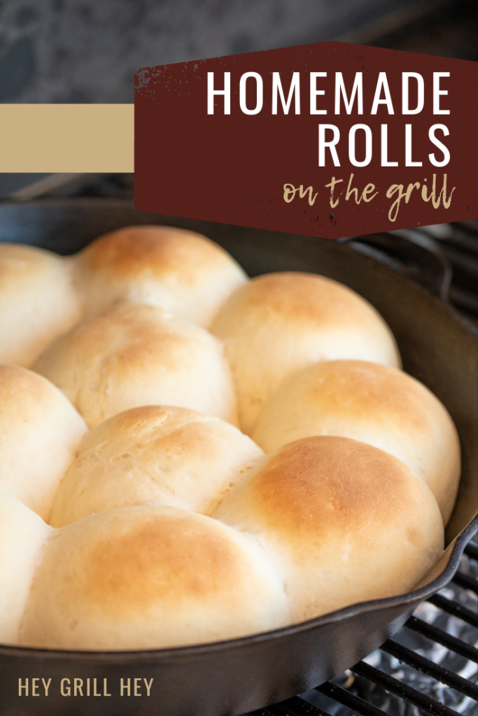 Golden brown rolls in a cast iron skillet on the grill grates of a smoker. Text overlay reads: Homemade Rolls on the Grill.