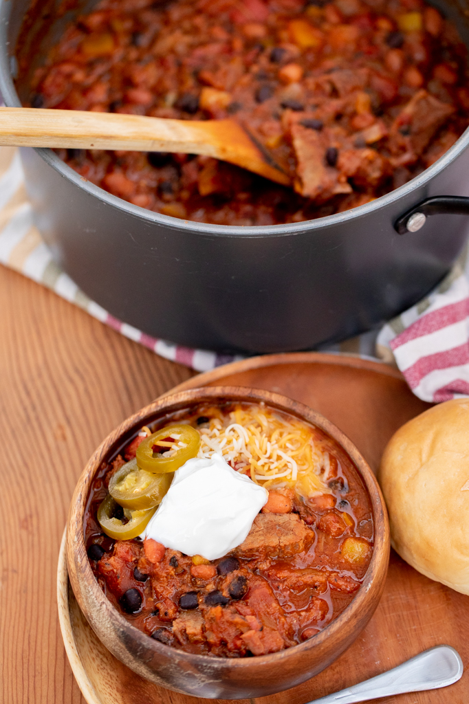 Bowl of brisket chili on a plate next to a roll and metal spoon with a pot of brisket chili in the background.
