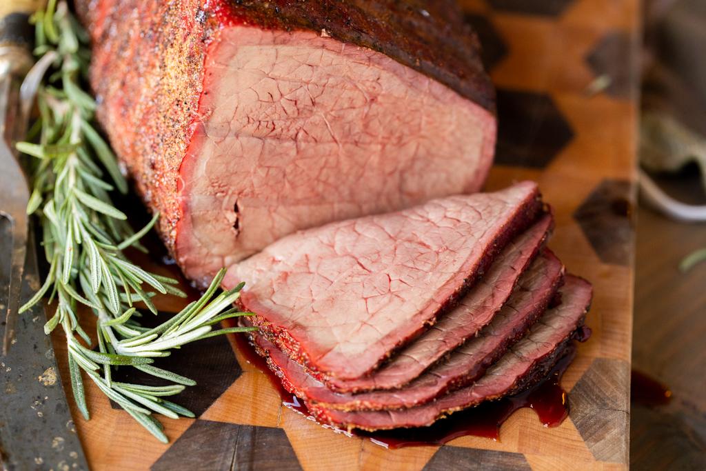 Sliced beef rump roast on a wooden cutting board next to fresh herbs.
