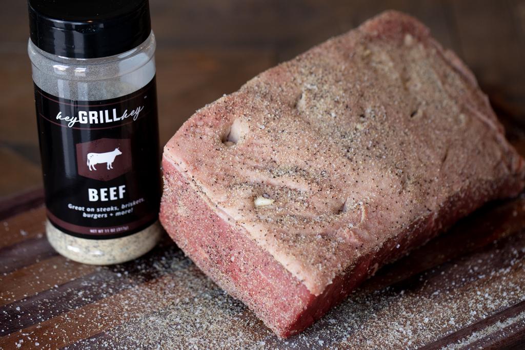 Whole uncooked rump roast seasoned with Hey Grill Hey Beef Seasoning next to a bottle of Beef Seasoning.