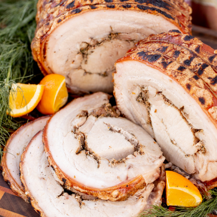 Sliced porchetta surrounded by lime wedges and fresh herbs on a wooden cutting board.