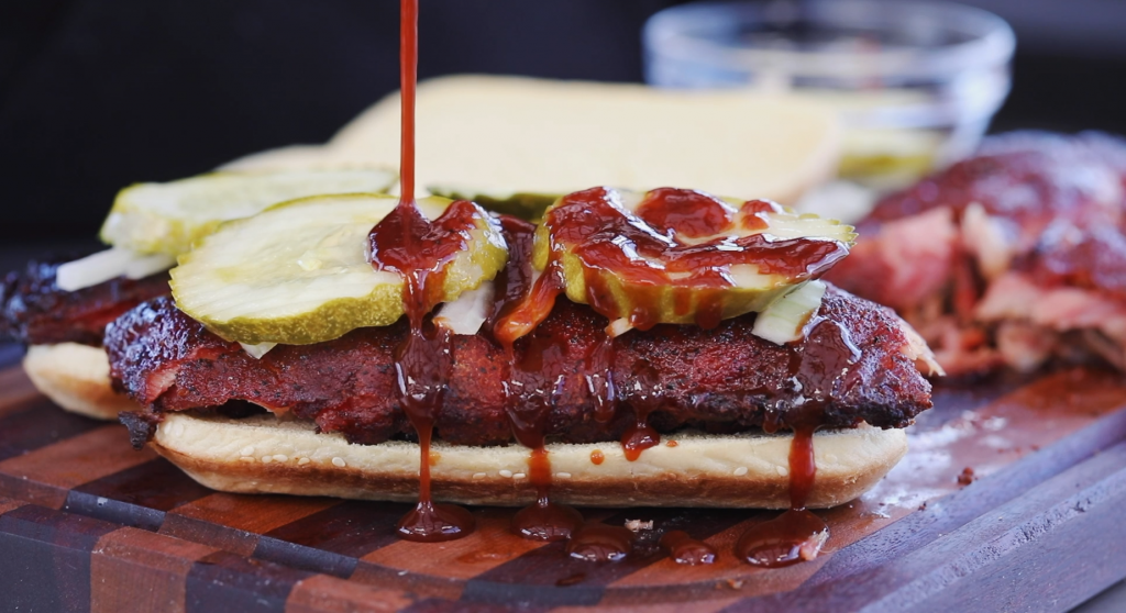 Everything BBQ Sauce being drizzled on a smoked rib sandwich.