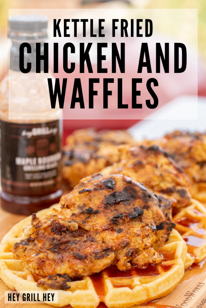 Four kettle fried chicken breasts on top of round waffles on a wooden cutting board with a bottle of BBQ sauce in the background. Text overlay reads: Kettle Fried Chicken and Waffles.