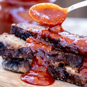 Texas BBQ Sauce being spooned over a stack of sliced brisket.