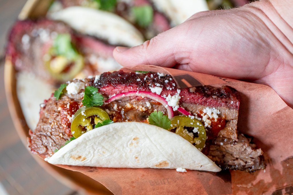 Hand holding a fully loaded beef brisket taco.