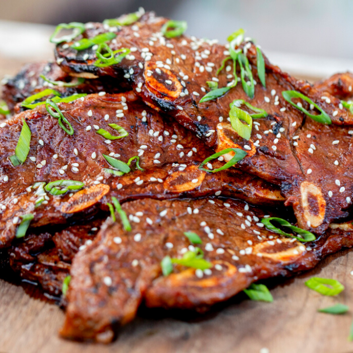 Kalbi garnished with sliced green onions and sesame seeds stacked on a round wooden serving board.